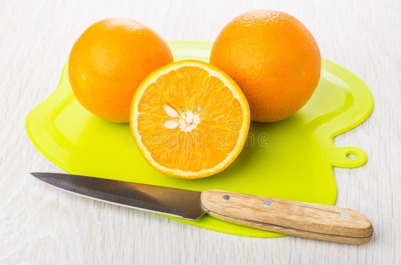 Hela apelsiner och halva av apelsinen på skärbrädan, kniv royaltyfria foton