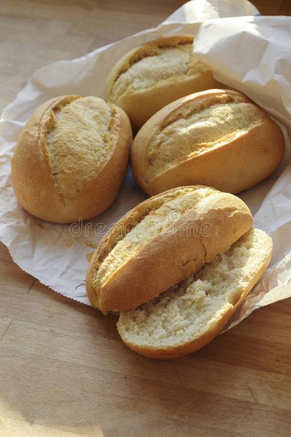 Hela brödrullar eller bullar och halverat nytt från bagerit i a royaltyfri foto