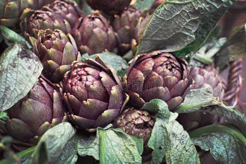 Hela kronärtskockagrönsaker med sidor som täckas i daggiga regndroppar arkivfoto