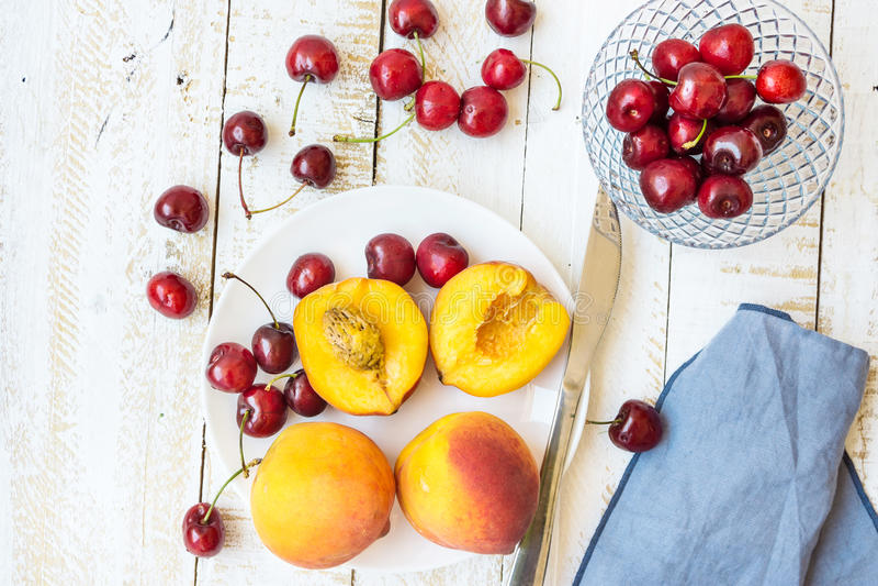 Hela mogna färgrika persikor som halveras och, söta körsbär på den vita plattan, crystal bunke, kniv, wood tabell för planka, blå royaltyfri bild