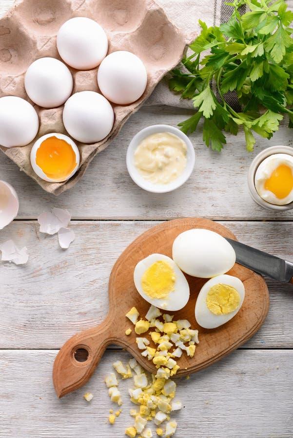 Hela och för snitt kokta ägg med sås på trätabellen fotografering för bildbyråer