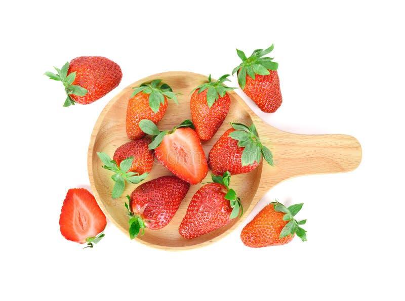 Hela och halva färska, mogna jordgubbar med blad i träplatta med vit bakgrund royaltyfria bilder