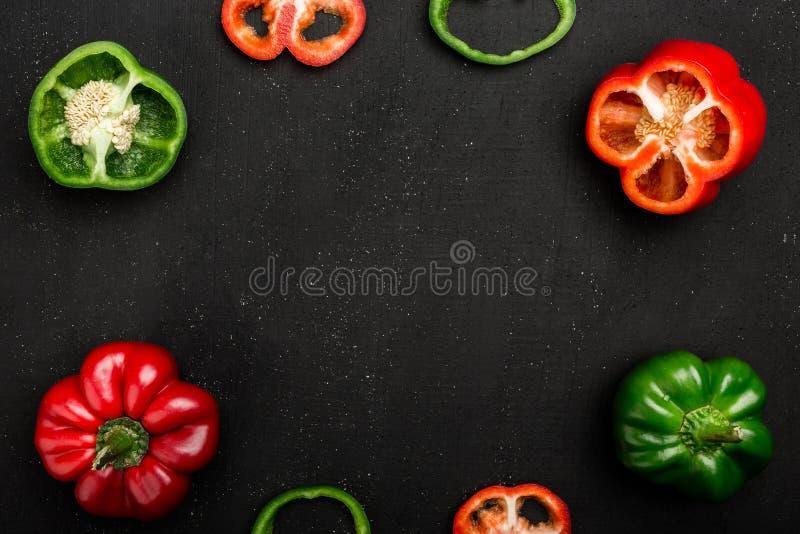 Hela röda och gröna spanska peppar eller söta peppar eller paprikor, snitt i halva och skivor på mörkt bräde royaltyfria bilder