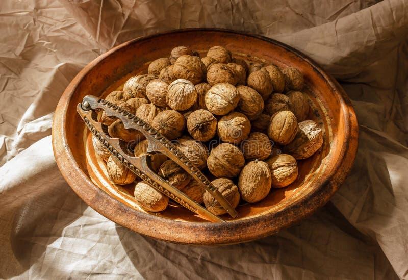 Hela valnötter i en tappninglerabunke och en nötknäppare med sunli royaltyfri bild