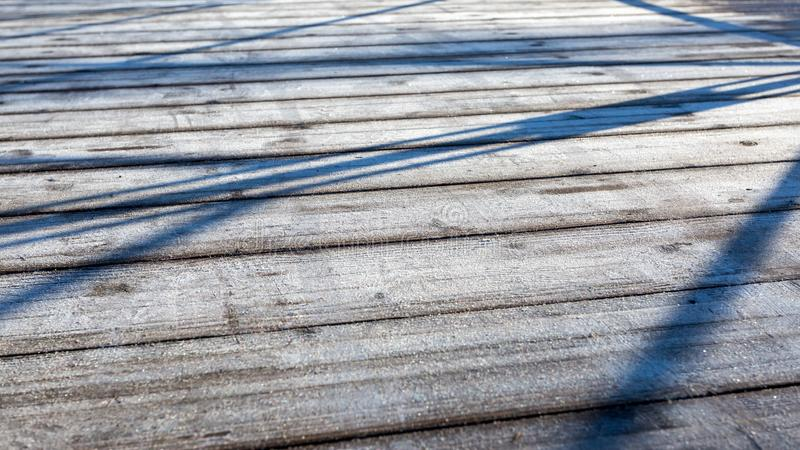 Helada de la mañana en el embarcadero de madera hecho de tableros Fondo de madera del invierno fotos de archivo