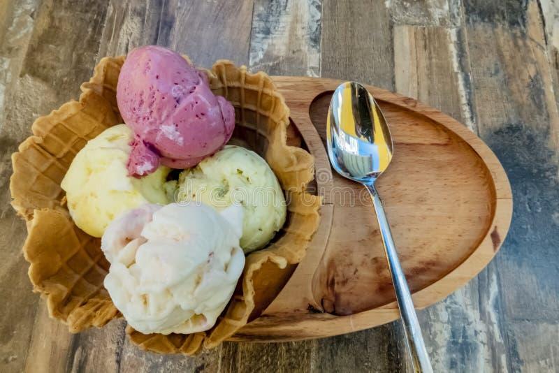 Helado con la fruta mezclada en cono del hielo con la placa y la cuchara de madera en la tabla foto de archivo