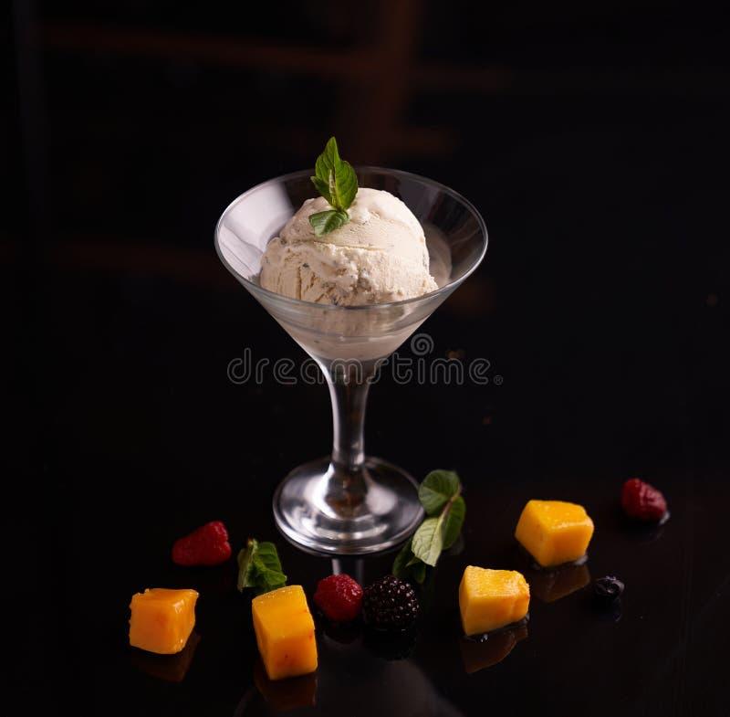 Helado con queso del mascarpone en un cuenco de cristal del helado adornado con las hojas de menta en un fondo oscuro con las reb fotografía de archivo libre de regalías