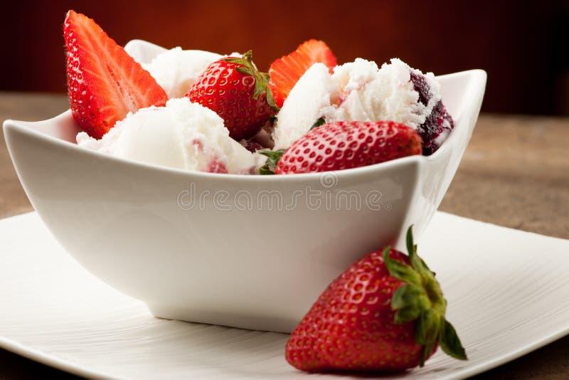 Helado de la fresa en un cuenco blanco con las fresas fotografía de archivo