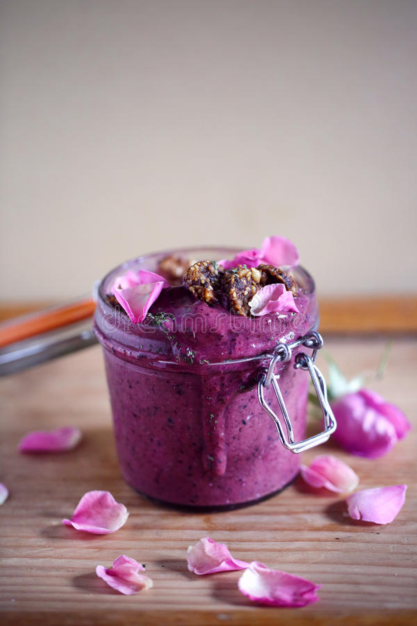 Helado de las remolachas y del arándano o cuenco del smoothie, tarro, con las galletas de la semilla y los pétalos color de rosa imagen de archivo libre de regalías