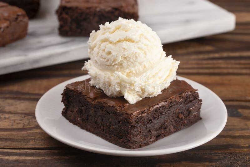 Helado doble de los brownie del chocolate con la crema de Vanilla Ice en el top fotografía de archivo libre de regalías