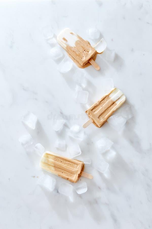 Helado quemado del café de la nata en un palillo de madera sobre el fondo de mármol, visión superior foto de archivo libre de regalías