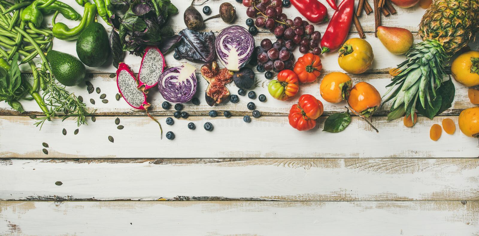 Helathy raw vegan food cooking background. Flat-lay of fresh fruit, vegetables, greens, superfoods over white rustic wooden table, top view, copy space. Clean stock image