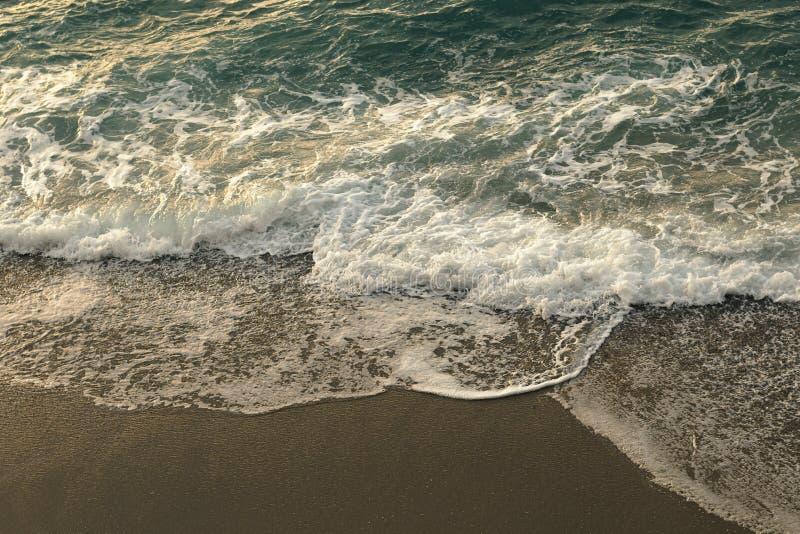 Heldendicht van overzees met golven en schuim wordt geschoten die op het strand morsen dat stock foto