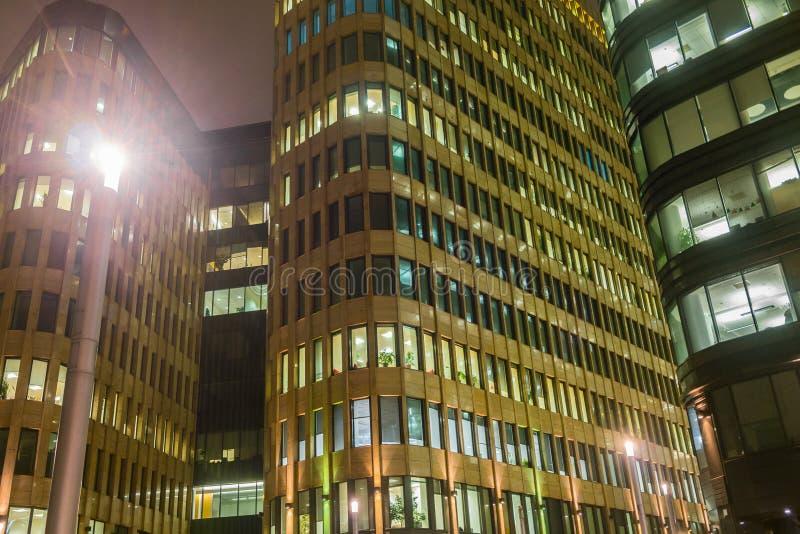 Helder aangestoken Vensters van moderne wolkenkrabbers Fonkelende futuristische nachtachtergrond stock foto