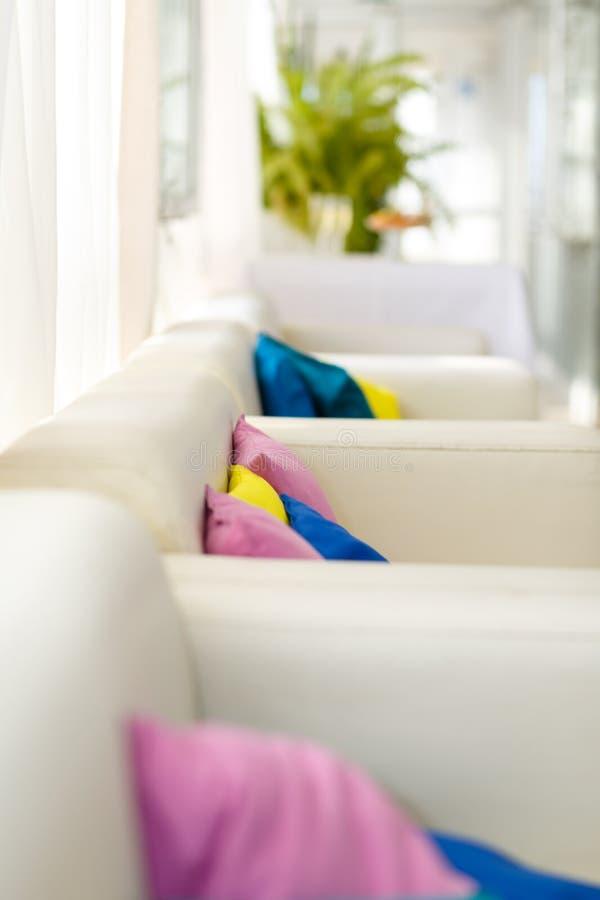 Helder binnenland met witte bank en kleurrijke hoofdkussens stock foto