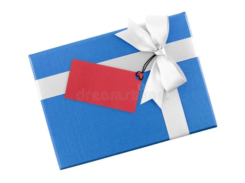Helder blauw giftvakje met witte lintboog en lege rode die document groetkaart voor het schrijven van bericht op witte achtergron royalty-vrije stock foto's