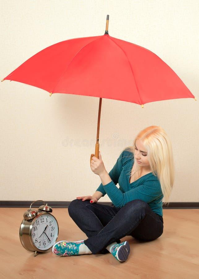 Helder blonde met een grote rode paraplu stock fotografie