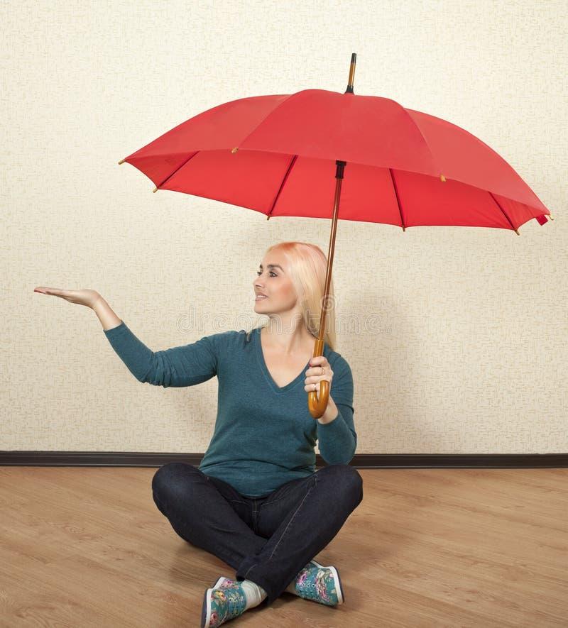 Helder blonde met een rode parapluzitting op de vloer stock fotografie