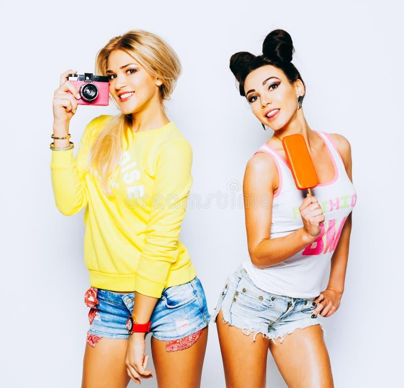 Helder de zomerportret van twee vrolijk meisjes, blonde en brunette Het hebben van pret, het genieten van van roomijs en het neme stock afbeelding