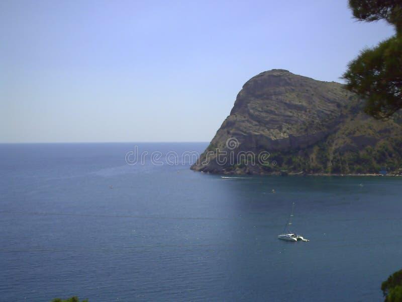 Helder, de zomerzeegezicht met de rotsachtige kust van de Zwarte Zee in de Krim dichtbij de stad & x22; Nieuwe Wereld royalty-vrije stock afbeelding