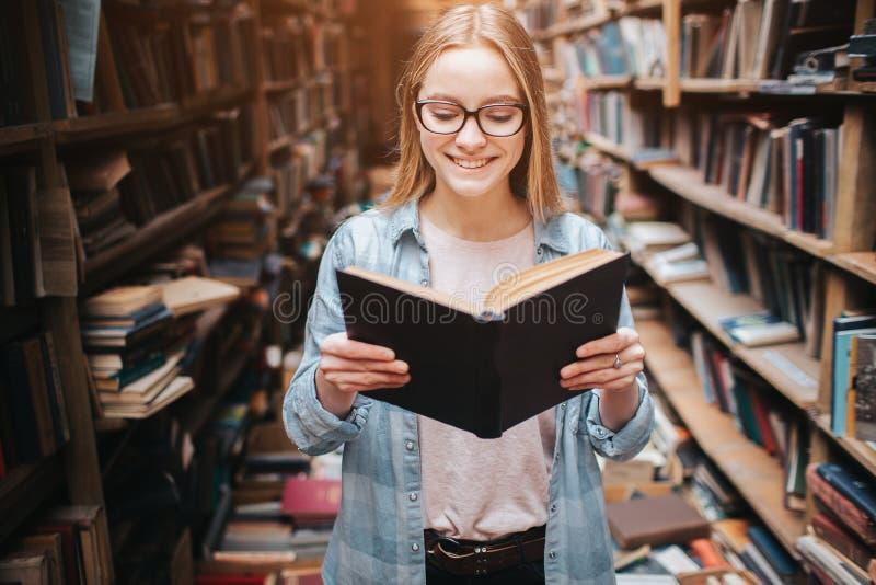 Helder en warm beeld van slimme student die een boek lezen Het meisje glimlacht en blijft boek verder lezen royalty-vrije stock fotografie