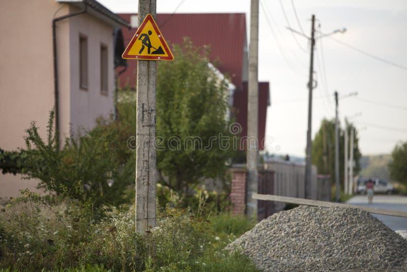 Helder geel driehoekig waarschuwingsbord; De aandacht, het werk vooruit, postte hoogte op concrete pijler in groen gras bij grint stock foto's