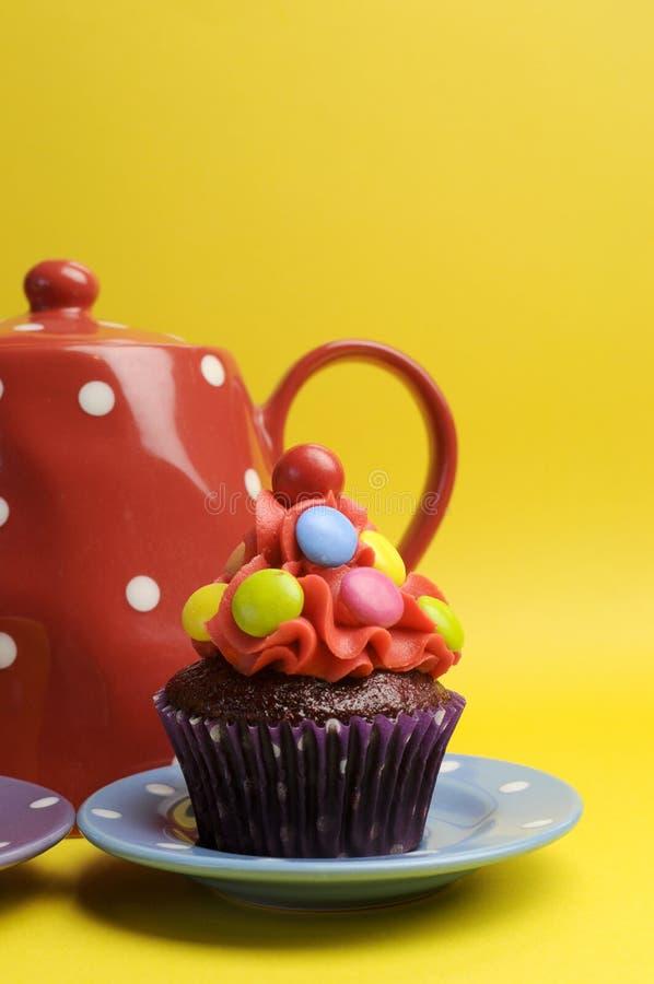 Helder gekleurd suikergoed cupcake met de pot en de kop van de stipthee - verticaal. royalty-vrije stock foto's
