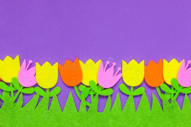 Helder gekleurde gevoelde tulpenbloemen op een duidelijke achtergrond stock foto's