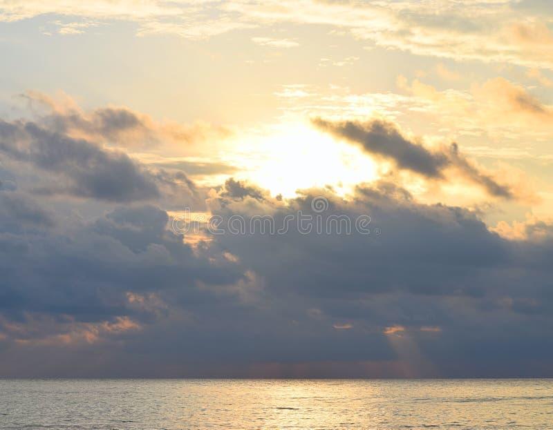 Helder Gouden Geel Zonlicht van Donker Grey Clouds in Hemel het uitspreiden over Oceaan met Bezinning in Water - Skyscape stock foto's