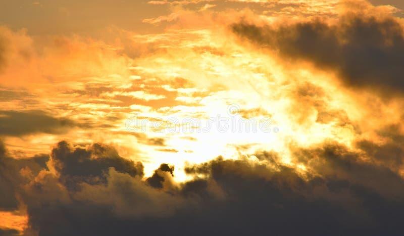 Helder Gouden Geeloranje Zonlicht van Donker Grey Clouds in Hemel - Warme Skyscape - Hitte en Zonne-energie royalty-vrije stock afbeeldingen