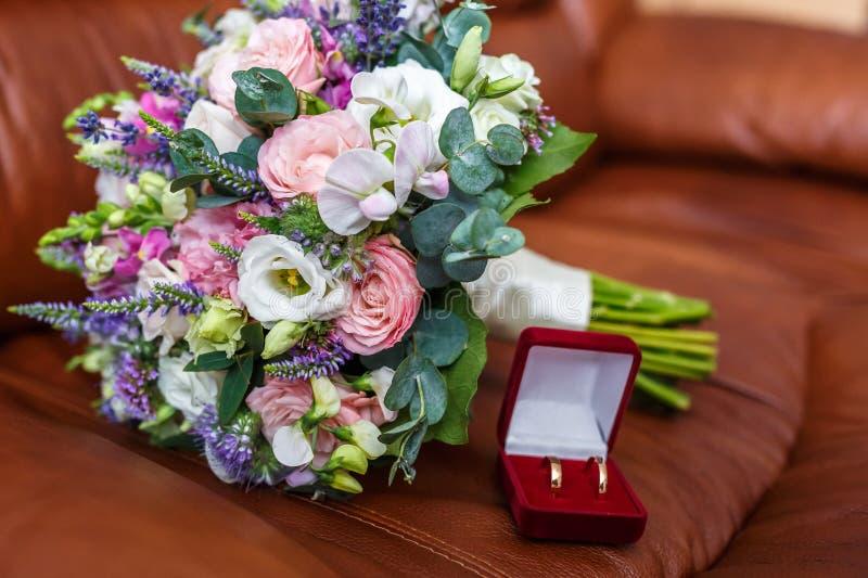 Helder huwelijksboeket van de zomer witte roze rozen en orchidee met violette wildflowers met trouwringen stock fotografie