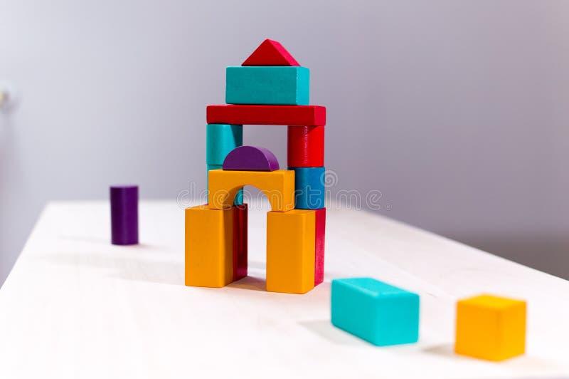 Helder kleurrijk houten blokkenstuk speelgoed Bakstenenkinderen die toren, kasteel bouwen Rood, sinaasappel en blauw royalty-vrije stock foto