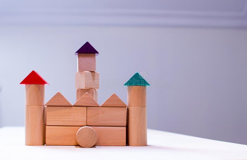 Helder kleurrijk houten blokkenstuk speelgoed Bakstenenkinderen die toren, kasteel, huis bouwen stock afbeeldingen