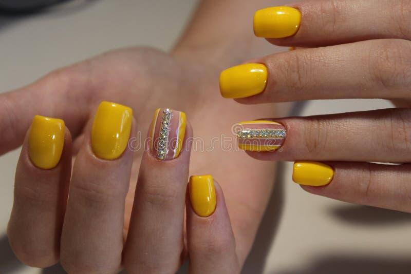 Helder manicureontwerp van gele spijkers stock foto