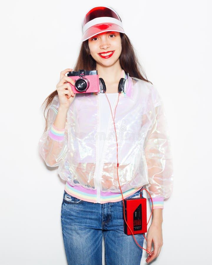Helder modieus portret van een jonge vrouw in een in uitrusting met een uitstekende cassettespeler, hoofdtelefoons en camera stock foto