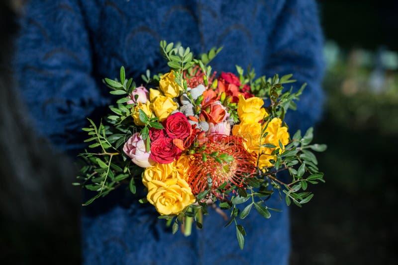 Helder ongebruikelijk elegant de herfstboeket in handen van het bloemistmeisje in de donkerblauwe laag stock foto