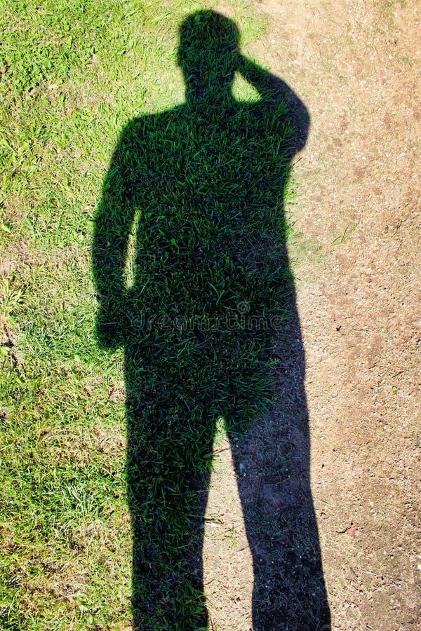Helder Schaduwgras van een mens in het zand royalty-vrije stock fotografie