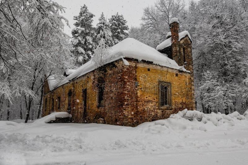 Helder sinaasappel verlaten huis in de sneeuw stock foto's