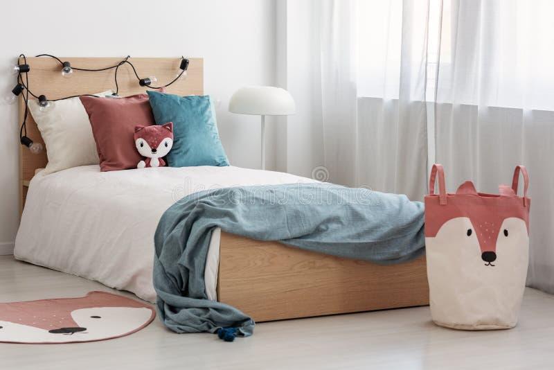 Helder slaapkamerbinnenland met eenpersoonsbed met turkooise deken op wit beddegoed en kleurrijk hoofdkussens en stuk speelgoed stock foto