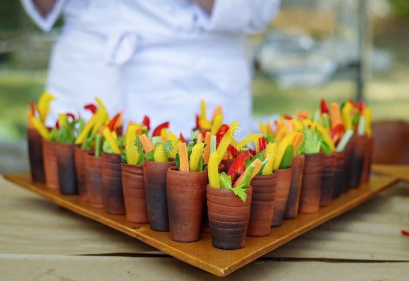 Helder stro dat verse groenten voor buffet snijdt dat in een cla wordt gediend stock afbeeldingen