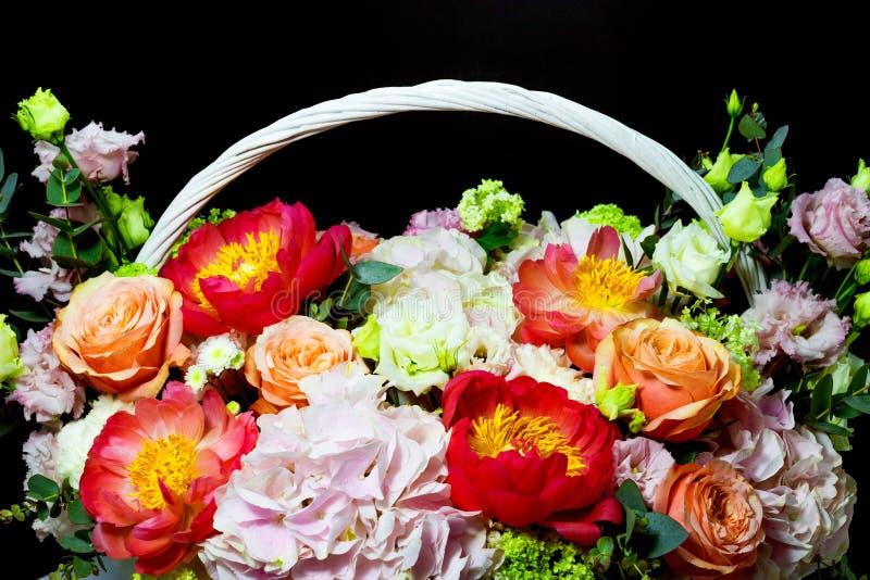 Helder wit bloemstuk in een mand op een donkere achtergrond stock foto's