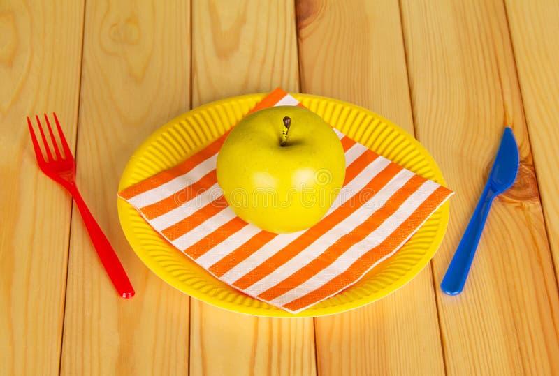Heldere beschikbare vaatwerk, servet en appel op licht hout als achtergrond stock foto