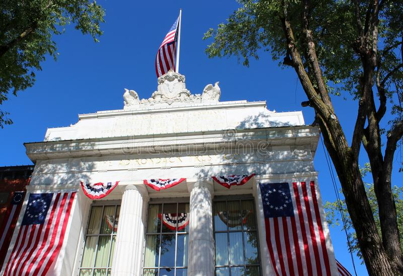 Heldere blauwe hemel achter Historische die architectuur in vlaggen, Adirondack-Vertrouwen, Saratoga, New York, 2018 wordt behand royalty-vrije stock afbeelding
