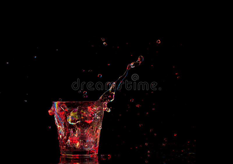 Heldere cocktail in glas en bespattend water op donkere achtergrond stock afbeelding