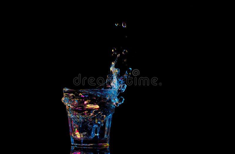 Heldere cocktail in glas en bespattend water op donkere achtergrond royalty-vrije stock foto's