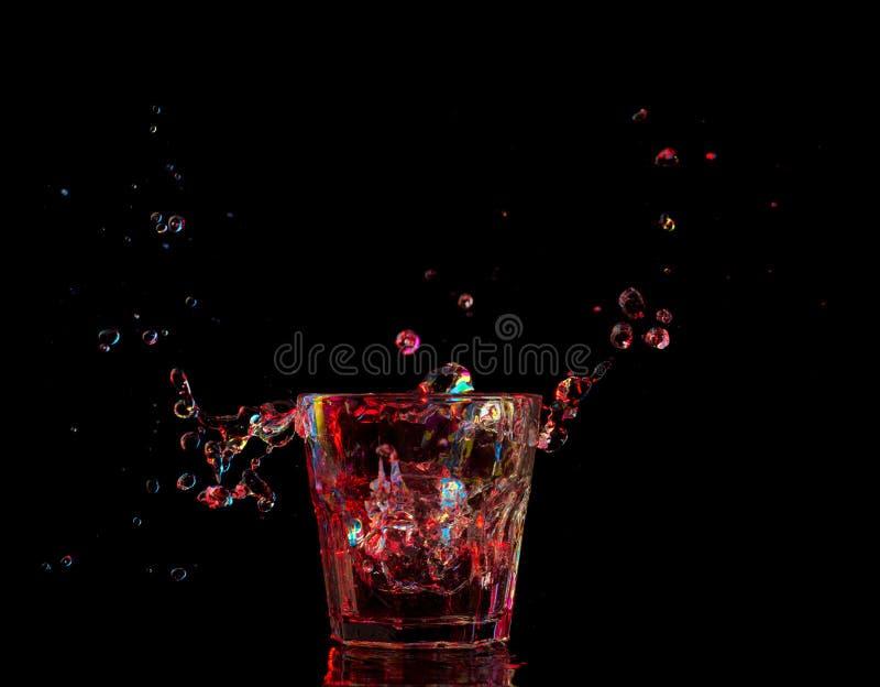 Heldere cocktail in glas en bespattend water op donkere achtergrond stock afbeeldingen