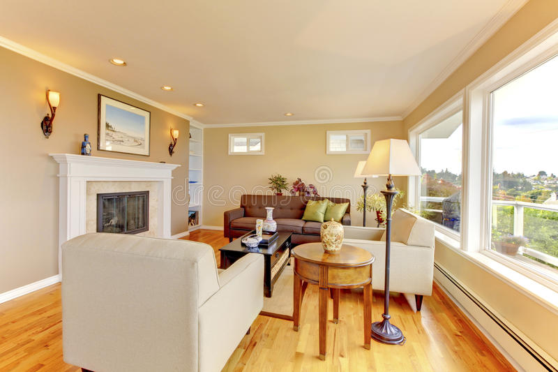 Heldere comfortabele woonkamer met beige muren en open haard stock afbeeldingen