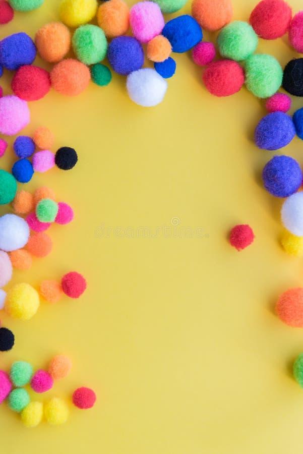 Heldere die multi-colored pom-poms als grens op een stevige gele achtergrond wordt geschikt royalty-vrije stock afbeelding