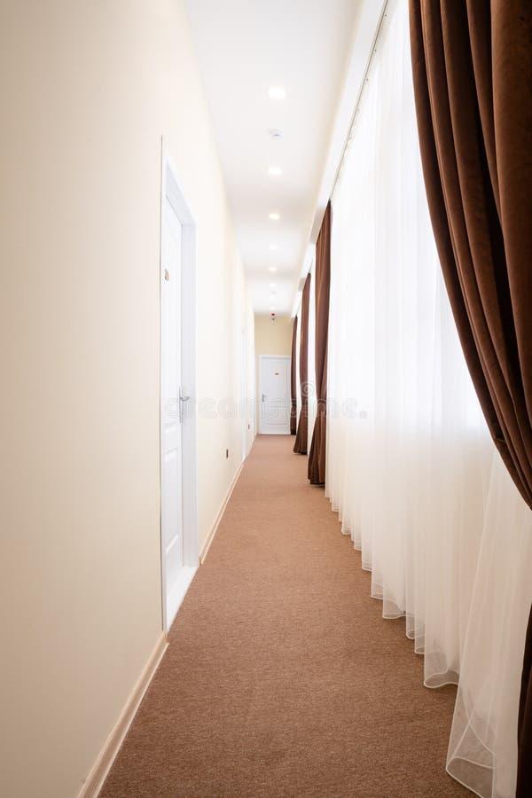 Heldere gang met witte deuren, bruin tapijt, de witte gordijnen van Tulle en bruine gordijnen royalty-vrije stock afbeeldingen