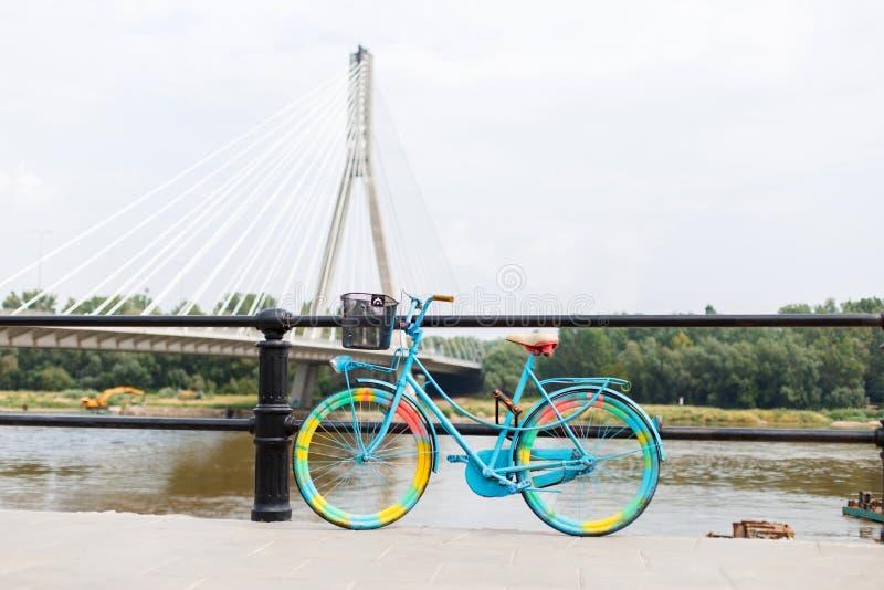 Heldere geel-blauwe fietsenrekken dichtbij de brug op de achtergrond van de rivier Stedelijke Levensstijl stock foto